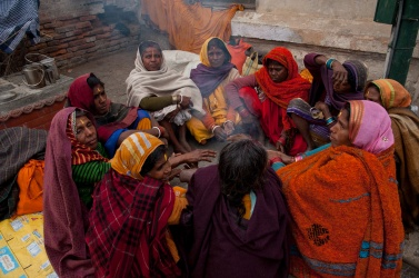 Women gather in a circle around a fire to warm up and pray together