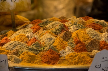 A mosaic of fragrant spices including turmeric, curry, cumin, chili pepper, cardamom.