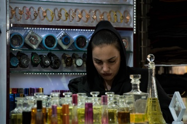 A young girl, with traditional but very made-up clothes, inside her small shop of watches and perfumes in the Bazar e Vakil of Shiraz