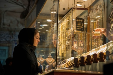 A young girl who admires one of the many windows of gold jewelry inside the Bazaar of Yazd.