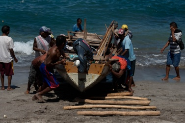 To bring the boats back to the beach, simple sticks are used to make it slide better. All the fishermen help themselves to make this difficult operation
