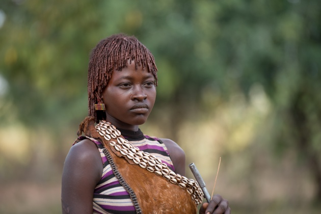 A girl Hamer with the typical hair, with braids dyed with red earth and mixed with butter