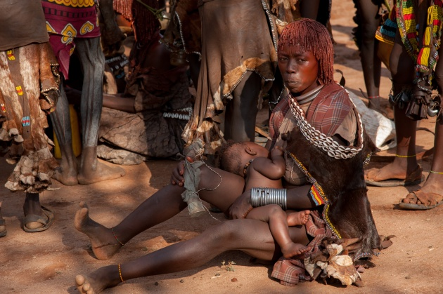 A Hamer woman who rests with her child, after walking several hours to reach the place of the ceremony