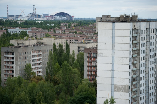 The city of Prypiat seen from the roof of one of the many abandoned buildings, and in the background the Chernobyl nuclear power plant