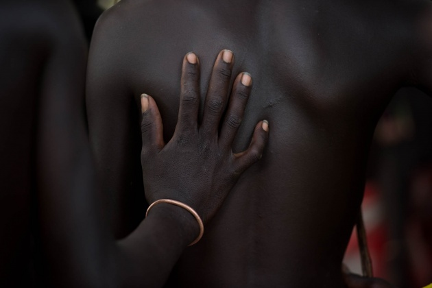 Omo valley Ethiopia. An ethnic Hamer boy, supports his hand with affection to his friend who has to face a very important trial.